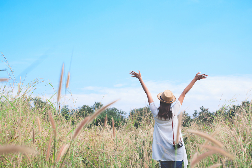 woman traveler with camera push hands and breathing at field of grasses and forest, wanderlust travel concept, space for text, atmosperic epic moment
